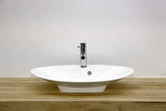 Wash Basin. Ceramic Wash Basin at Wooden Counter in Contemporary Bathroom Royalty Free Stock Images