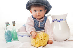 Wash basin funny baby. Four months old baby with cap in a wash basin with sponge Stock Photo