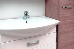 Wash basin modern sink in the bathroom. Chrome-plated water mixer. The mirror above the sink. Wash basin modern sink in the bathroom. Yellow water mixer stock photos
