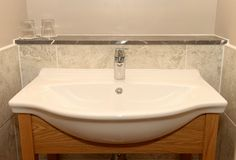 Bathroom sink. Wash basin with single tap on a wooden (oak) frame  in the bathroom with tiled surround and glasses on a marble shelf Royalty Free Stock Photos