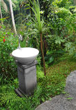 Wash basin with tap, outdoor garden. A photograph of a white marble stone washing basin with silver stainless steel metal tap, placed outdoors in tropical garden stock photo
