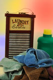 Who's Doing Laundry Today?. Pile of dirty towels with an old fashion washboard and a container of laundry soap with a multicolor background Stock Image