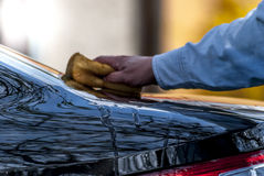 Wash car. Hand with yellow sponge wash of a black car stock photo