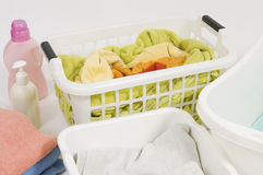 Wash colored laundry. Detergents and towels in white plastic basket, basket with colorful laundry to wash (handwash Stock Photo