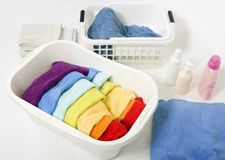 Wash colored rainbow laundry. Wash colored laundry. Detergents and towels in white plastic basket, basket with colorful rainbow laundry to wash Stock Photography