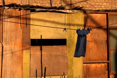 Single Item of Clothing Pegged to Clothes Line. Single item of clothing on clothes line secured with pegs with yellow and orange timber background stock photo