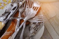 Wash dirty dishes: forks and plates with a pattern in soapy water in the kitchen sink. Cleanliness and order in the house. royalty free stock images