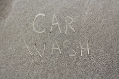 Wash finally that the machine. Inscription on a dirty unwashed auto, car wash Stock Image