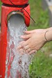 Wash hands under the jet of water from a fire hydrant. Wash hands under the powerful jet of water from a fire hydrant Royalty Free Stock Image