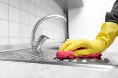 Wash kitchen sink. Hands in yellow gloves washing the kitchen sink royalty free stock photo