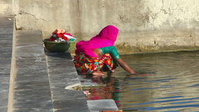 Wash in the lake. A woman washes clothes in the lake stock footage
