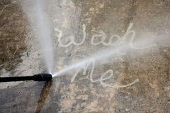 Wash Me. The words WASH ME on a dirty sidewalk with the nozzle of a power washer spraying water Royalty Free Stock Images