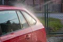 Wash the red car with a stream of water Royalty Free Stock Images