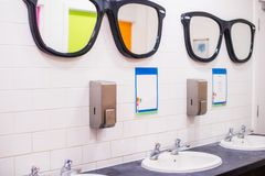 Wash sink and big mirrors in the shape of glasses in public toilet , row of english two cranes wash basin in restroom. Selective. Focus, copy space royalty free stock photo
