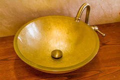 Washbasin in golden leaf and brass faucet Royalty Free Stock Images