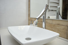 Washbasin with mixer tap in a bathroom Stock Images