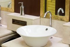 Washbasins, taps and mirror in public toilet Stock Image