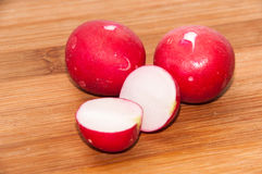 Washed and chopped radishes on the wooden board Stock Photo
