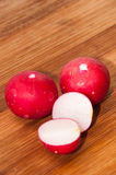 Washed and chopped radishes on the wooden board Royalty Free Stock Photography