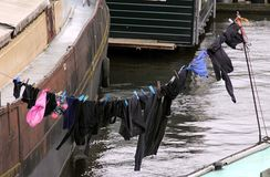Washed clothes drying in the sun on the boathouse stock images