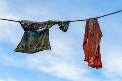 Washed clothes with snow on it, left behind outside, drying on the clothesline in the winter. Blue sky and white clouds. Two pieces of washed clothes with some royalty free stock photography