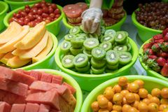 Washed and cut fruit sorted in bright green bowls stock image