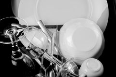 Washed dishes. Black and white  closeup photo of shinny washed forks, spoons, glasses, coffe cup an other white dishes on black background Royalty Free Stock Image