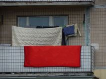 The washed laundry is dried on the balcony of the house. The washed laundry is dried on the balcony stock photo