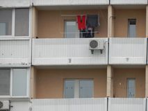 The washed laundry is dried on the balcony of the house. The washed laundry is dried on the balcony stock photography