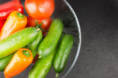 Washed organic vegetables in bowl on dark stone plate, top view Royalty Free Stock Images