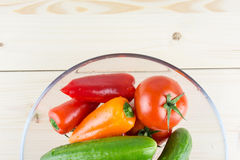 Washed organic vegetables in bowl on wooden bacKground, top view Royalty Free Stock Image