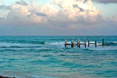 Washed out ocean dock in the ocean. Remaining posts of washed out dock on the beaches of Mexico royalty free stock photos