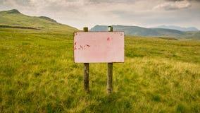 Washed out and unreadable Warning sign. On top of Moel yr Hydd near Blaenau Ffestiniog, Gwynedd, Wales, UK Royalty Free Stock Photos