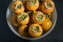 Washed persimmons in a bowl royalty free stock image