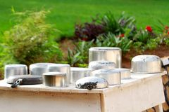 Washed saucepans drying on a table outside a cottage. Under the afternoon sun. Pots and pans and frying pans on a wooden table near a beautiful garden Royalty Free Stock Photography