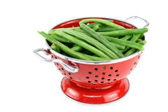 Washed string beans in red colander. Royalty Free Stock Photo