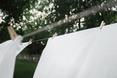 Washed towels are hanging on the rope. Linen is dried. Clothespin on a towel that is dried. Drying linen in the garden royalty free stock photo