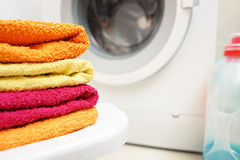 Washed towels stacked with washing machine in background Royalty Free Stock Photo