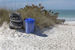 Washed up tires  next to a recycle bin on St. Pete Beach, Florida Royalty Free Stock Images