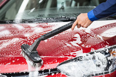 Washer Cleaning Red Car At Service Station Stock Images