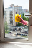 Washer cleans window by rag in apartment house Royalty Free Stock Images