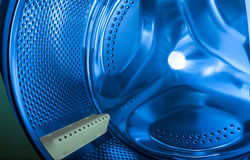 Washer interior. Interior view of the washer in blue with white detail Stock Image