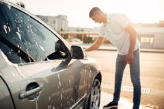 Washer rubbing vehicle with foam, car wash. Washer rubbing vehicle with foam, automobile in suds, car wash. Carwashing station Royalty Free Stock Photo