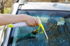 Washes and cleans the glass of a car . Royalty Free Stock Photos