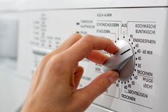 Washing. A hand is adjusting the washing program on a washing machine (German Text Royalty Free Stock Images