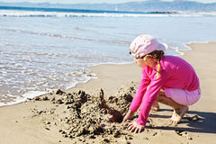 Washing away a sandcastle Stock Photography