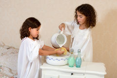 Washing before bedtime. Cute vintage victorian girls in nightgowns washing before bedtime stock photos
