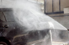 Washing black car by pressure washer gun  in car-wash shop Stock Photo