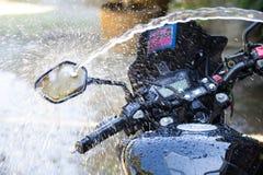Washing black motorcycle. A man are washing black motorcycle Stock Photography