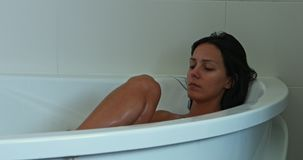 Washing body in bath. Young brunette woman taking bath with bubble and washing body stock video footage